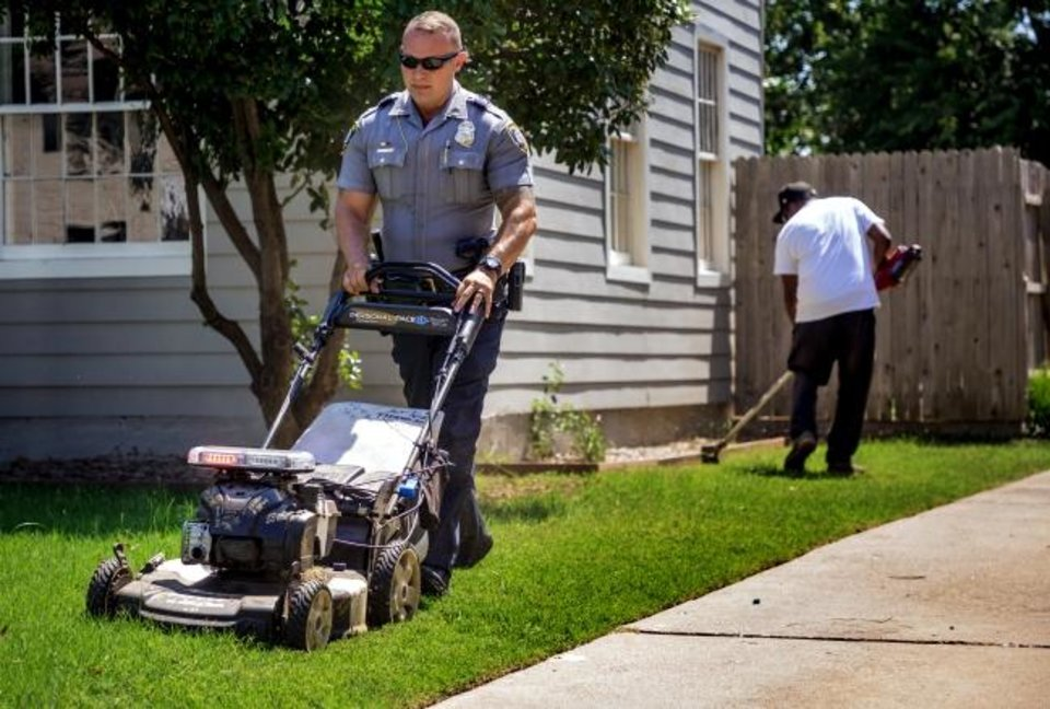 Photo -  Oklahoma City Police Lt. Taylor Shaw helps Rodney Smith mow at an Oklahoma City home as part of a program aimed at helping elderly, disadvantaged, disabled people and veterans with yard work. [Chris Landsberger/The Oklahoman]