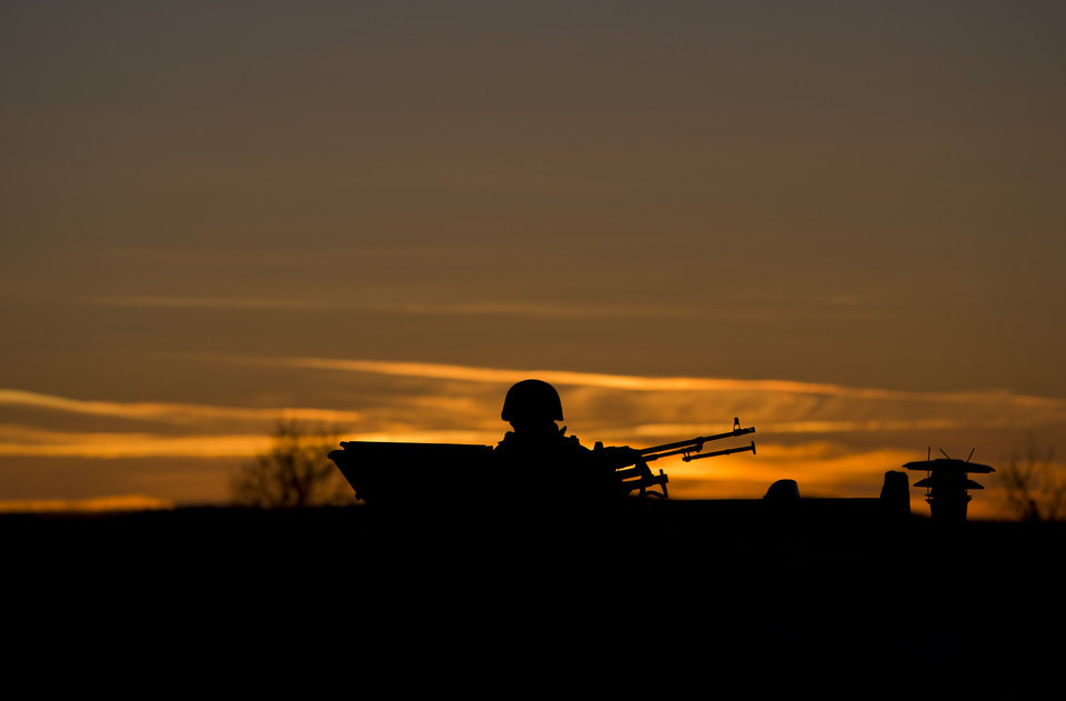 Photo - A pro-Russian soldier is silhouetted by the sunset sky as he mans a machine gun outside a Ukrainian military base in Perevalne, Ukraine, Saturday, March 15, 2014. Tensions are high in the Black Sea peninsula of Crimea, where a referendum is to be held Sunday on whether to split off from Ukraine and seek annexation by Russia. (AP Photo/Vadim Ghirda)