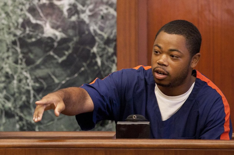 Photo - Kristopher Pratt points while identifying Ed Thomas during Thomas' trial at the Washtenaw County Trial Court in Ann Arbor, Mich., on Thursday, July 24, 2014. Thomas is on trial for the fatal shooting of Eastern Michigan University football player Demarius Reed.  (AP Photo/The Ann Arbor News, Patrick Record) LOCAL TELEVISION OUT; LOCAL INTERNET OUT