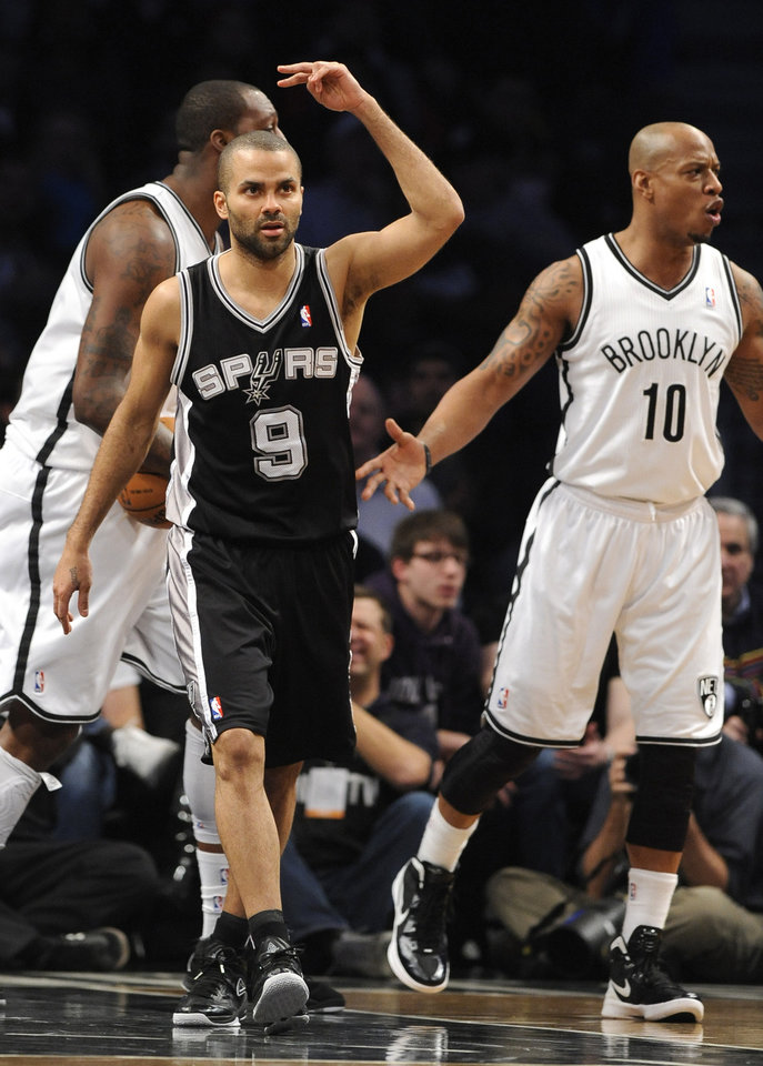 San Antonio Spurs' Tony Parker (9) and Brooklyn Nets' Keith Bogans (10) react after Parker scored in the first half of an NBA basketball game, Sunday, Feb. 10, 2013, at Barclays Center in New York. (AP Photo/Kathy Kmonicek)