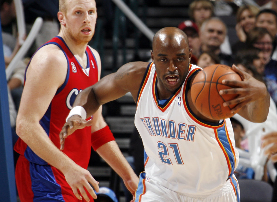 Photo - L.A. CLIPPERS: Damien Wilkins of the Thunder grabs a loose ball in front of Chris Kaman of the Clippers in the second quarter of the NBA basketball game between the Oklahoma City Thunder and the Los Angeles Clippers at the Ford Center in Oklahoma City, Wednesday, Nov. 19, 2008. BY NATE BILLINGS, THE OKLAHOMAN ORG XMIT: KOD