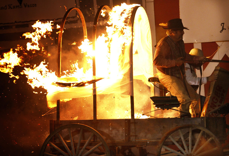 Photo - A blazing conestoga wagon enters the arena during one of the acts at the Pawnee Bill Wild West Show in Pawnee, Oklahoma on Saturday,  June 23, 2012.  Photo by Jim Beckel, The Oklahoman