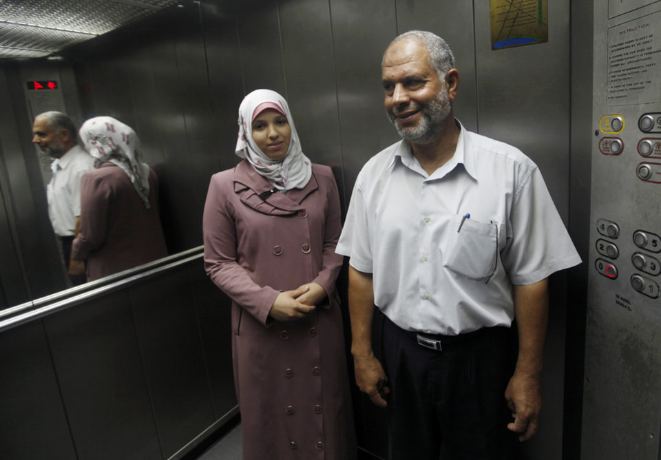 Photo - In this Monday, June 24, 2013 photo, Nabhan Rantisi, 58, and his 15-year-old daughter Roaa get on an elevator at Al-Aqsa college in Gaza City. On the day of his induction, Baraa Rantisi, Nabhan's nephew, was told to wait near a mosque. A white car drove up. Secret passwords were exchanged. And then he was sworn into the Muslim Brotherhood, an exclusive movement that sees itself on a divine mission to establish Islamic rule. AP reporters got rare access to the Rantisi family, the closest thing to a royal clan in the Brotherhood in Gaza, at a time when the movement is under siege throughout the region. (AP Photo/Hatem Moussa)