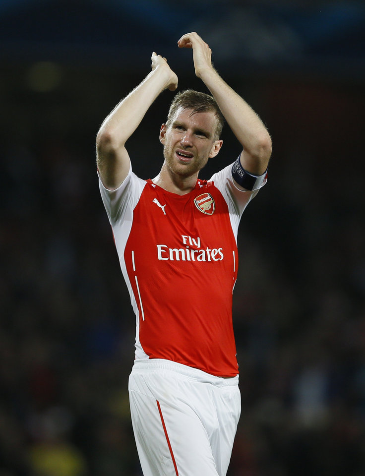 Photo - Arsenal's Per Mertesacker applauds the fans at the end of their second leg Champions League qualifying soccer match between Arsenal and Besiktas at Emirates Stadium in London Wednesday, Aug. 27, 2014. Arsenal won the game 1-0. (AP Photo/Kirsty Wigglesworth)