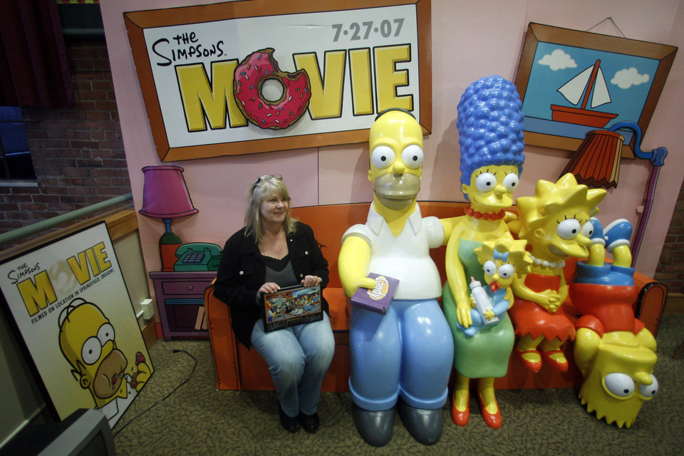 Photo -   Debra Gruell, Executive Director of the Springfield Museum, sits on the The Simpsons Couch at the museum Tuesday, April 10, 2012, in Springfield, Ore. One of the best-kept secrets in television history has been revealed, with