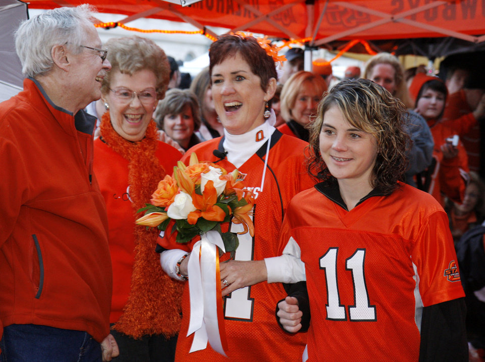 Photo - Jamie Walker, right, escorts her mother Yvonne Marsh down the aisle at Cowboy fans Scott Stuart and Yvonne Marsh wedding before the college football game between the University of Oklahoma Sooners (OU) and Oklahoma State University Cowboys (OSU) at Boone Pickens Stadium on Saturday, Nov. 29, 2008, in Stillwater, Okla. 