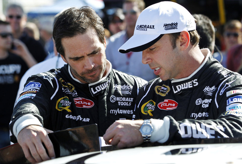 Photo - FILE - In this Nov. 11, 2012 file photo, Jimmie Johnson, left, talks with crew chief Chad Knaus prior to the NASCAR Sprint Cup Series auto race at Phoenix International Raceway in Avondale, Ariz. When asked about how dominating the pair has been since they partnered in 2002, the relentless Knaus replied: