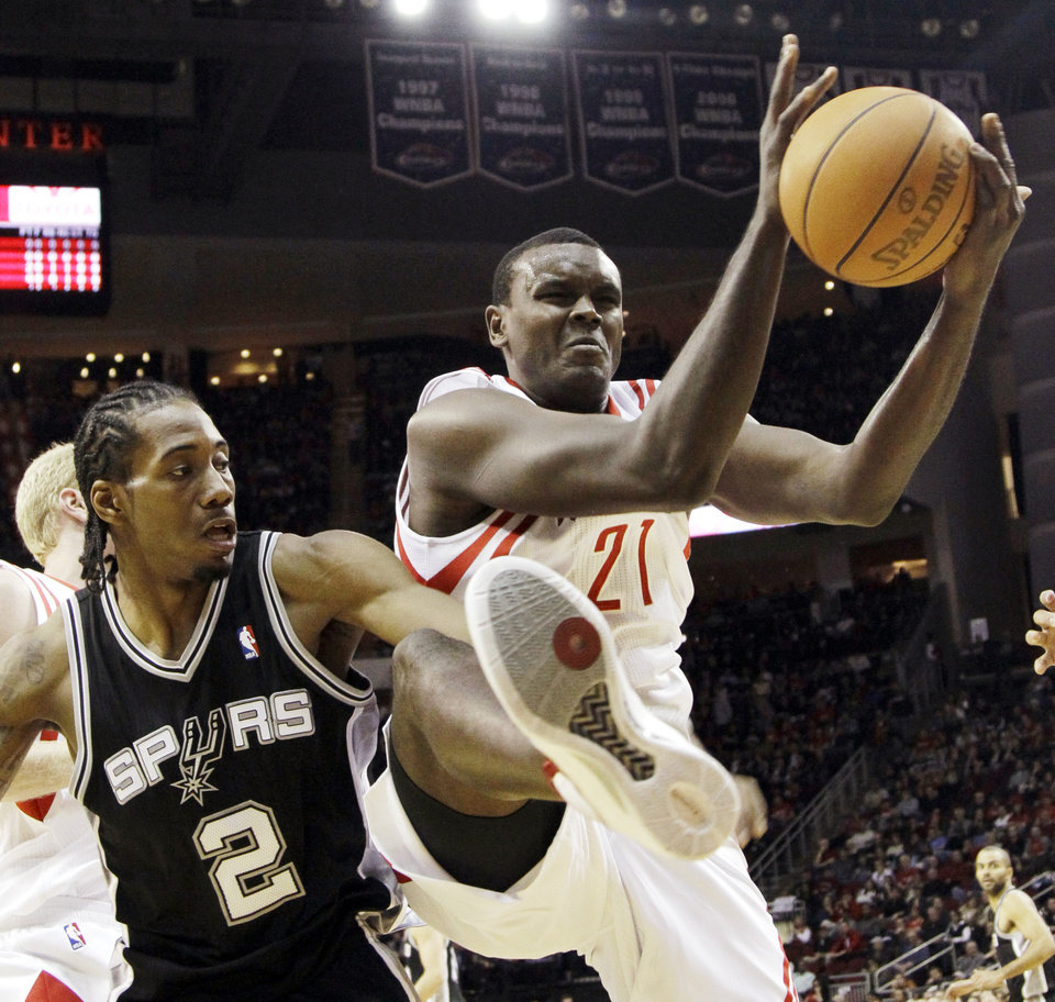 Photo -   FILE - In this Dec. 29, 2011 file photo, Houston Rockets' Samuel Dalembert (21) pulls down a rebound in front of San Antonio Spurs' Kawhi Leonard (2) during the first quarter of an NBA basketball game, in Houston. Dalembert lost a cousin and several close friends among the estimated 300,000 killed when a magnitude-7.0 earthquake rumbled across his native Haiti on Jan. 12, 2010. Two years later, the NBA's only Haitian-born player prays for progress, while tempering his frustration that more hasn't been done to rebuild his crippled country. (AP Photo/David J. Phillip, File)