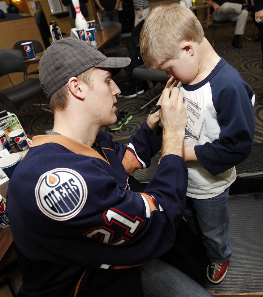 CHILD / CHILDREN / KIDS: Barons player Tanner House (21) signs  9-year-old Reis Wathen's shirt during the Barons Buddies event with the Oklahoma City Barons AHL hockey team and Special Olympians at AMF Sunny Lanes bowling alley in Del City, Okla., Wednesday, Jan. 25, 2012. Photo by Nate Billings, The Oklahoman