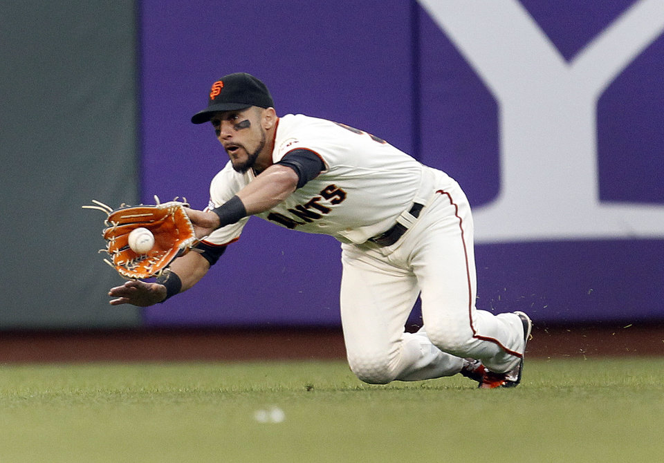 Photo - San Francisco Giants left fielder Andres Torres makes a diving catch on a hit by Chicago Cubs' Nate Schierholtz during the sixth inning of a baseball game on Saturday, July 27, 2013, in San Francisco. (AP Photo/Tony Avelar)
