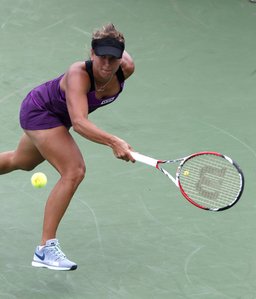 Photo - Barbara Zahlavova Strycova, from Czech Republic, returns a volley to Mona Barthel, from Germany, during a first round match at the Western & Southern Open tennis tournament, Tuesday, Aug. 12, 2014, in Mason, Ohio. (AP Photo/David Kohl)