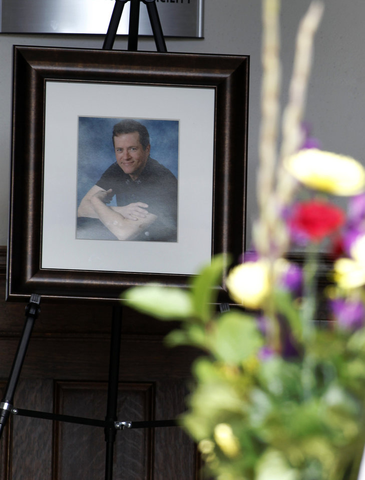 Photo -   Flowers arrive as a portrait is seen at the entrance for at a memorial service for Gordon Cowden Wednesday, July 25, 2012 in Denver. Cowden was one of 12 people killed, and over 50 wounded in a shooting attack early Friday at the packed theater during a showing of the Batman movie,