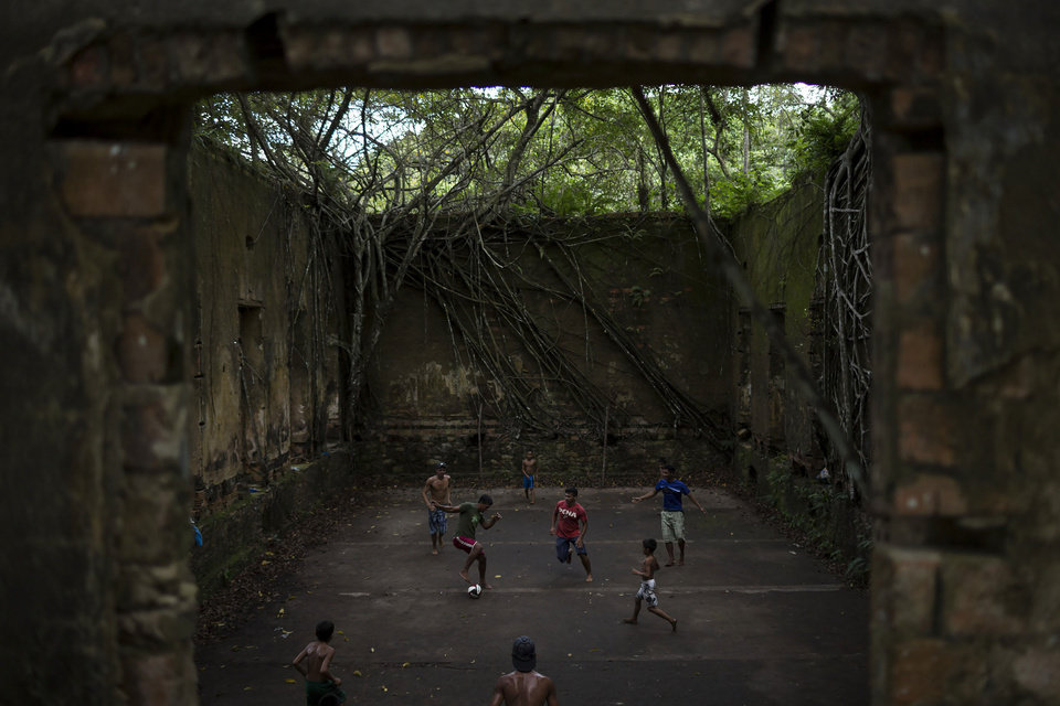 Photo - In this May 21, 2014 photo, Children and adults play soccer in the ruins of Paricatuba, near Manaus, Brazil. After the Italian migration dried up, the villa housed an art school run by French priests. The building's decline over the next century mirrored that of Manaus, which after the rubber boom went bust, slipped into a long period of decadence and decay. Then it became a penitentiary. Then a leper colony, before simply being abandoned to the tropical elements. (AP Photo/Felipe Dana)