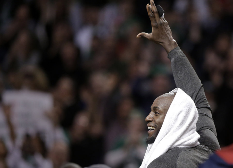 Photo - Brooklyn Nets forward Kevin Garnett, formerly of the Boston Celtics, waves to the crowd during a tribute to him in the first half of an NBA basketball game against the Boston Celtics, Sunday, Jan. 26, 2014, in Boston. (AP Photo/Steven Senne)
