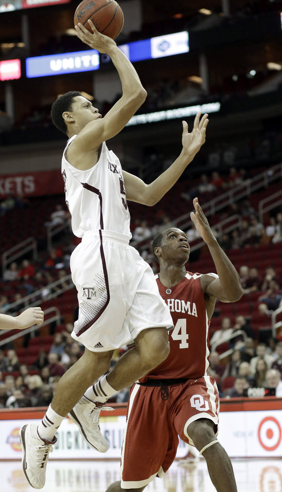 Texas A&M's Jordan Green, left, shoots over Oklahoma's Buddy Hield during the first half of an NCAA college basketball game Saturday, Dec. 21, 2013, in Houston. (AP Photo/Pat Sullivan)