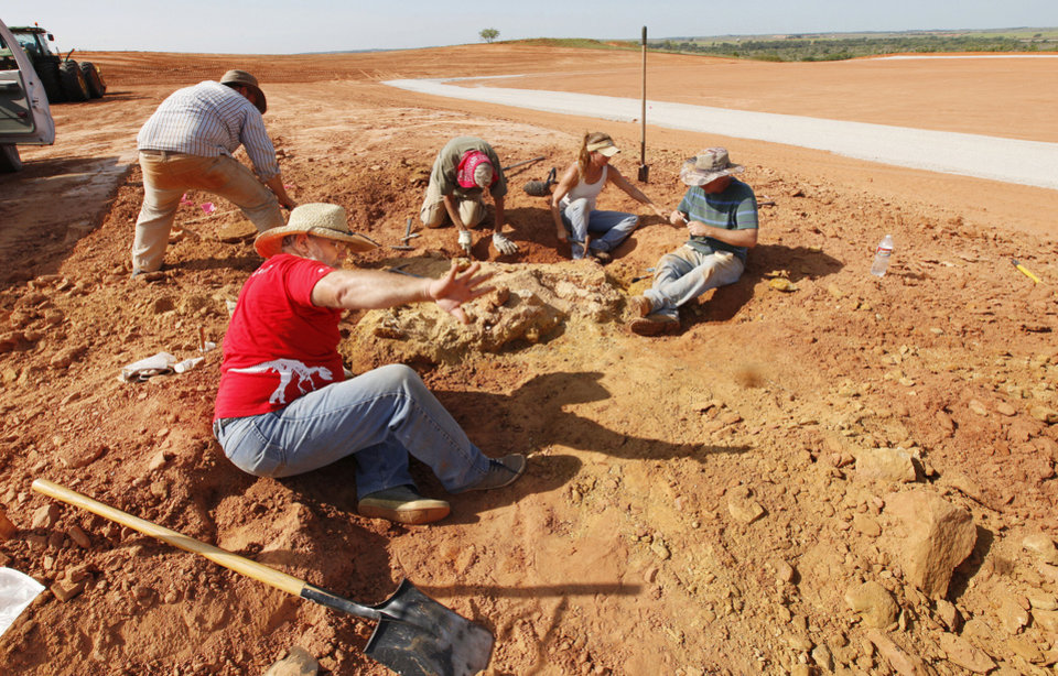 Photo - Paleontologist Kyle Davies, foreground, fossil preparator with the Sam Noble Oklahoma Museum of Natural History, tosses debris away as archaeologists and paleontologists dig fossilized bones from pit C on an Apache Corp. drilling site at the Packsaddle Wildlife Management Area in Ellis County south of Arnett Thursday, Aug. 22, 2013.  Teeth and bone fossils found at the site included those from prehistoric camels and horses. Photo by Paul B. Southerland, The Oklahoman  PAUL B. SOUTHERLAND - PAUL B. SOUTHERLAND
