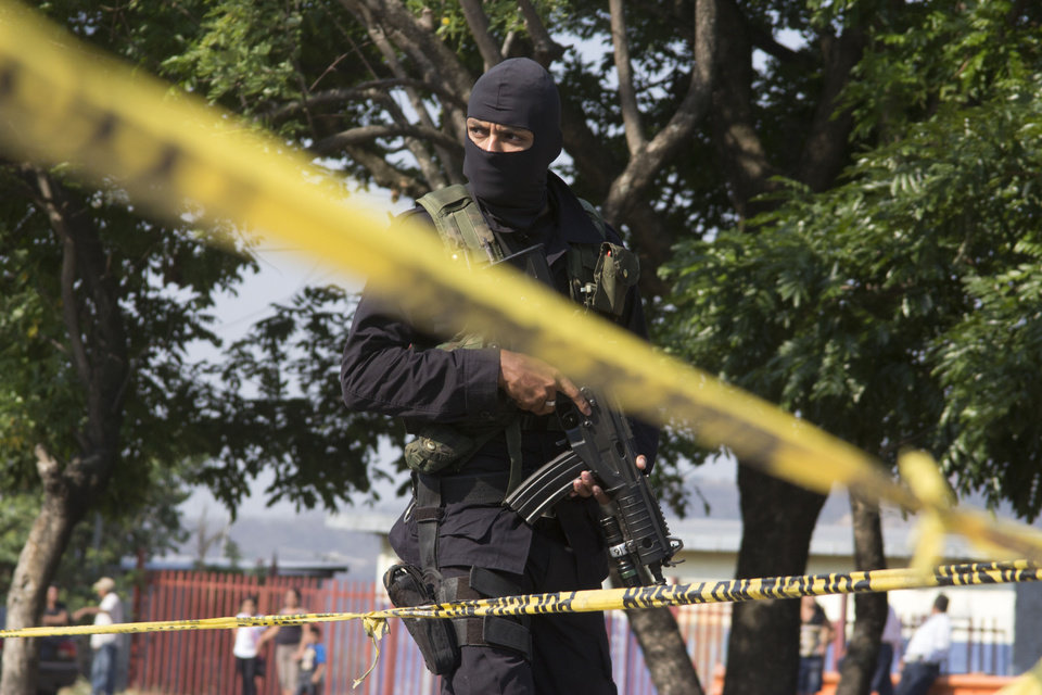 Photo - FILE - In this April 13, 2014 file photo, a police officer guards the scene after gunmen using assault weapons opened fire, killing four men in Santiago Texacuangos, 20 kms. south of San Salvador, El Salvador. In El Salvador 2.1 percent of the population, have been forced to leave their homes, the vast majority due to gang extortion and violence, according to U.N. figures. That's more than twice the percentage displaced by Colombia's brutal civil war, the U.N. says. (AP Photo/Salvador Melendez, File)