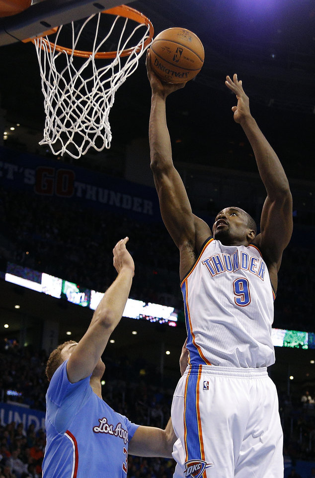 Photo - Oklahoma City 's Serge Ibaka (9) shoots over Los Angeles' Blake Griffin (32) during the NBA game between the Oklahoma City Thunder and the Los  Angeles Clippers at the Chesapeake Energy Arena, Sunday, Feb. 23, 2014. Photo by Sarah Phipps, The Oklahoman