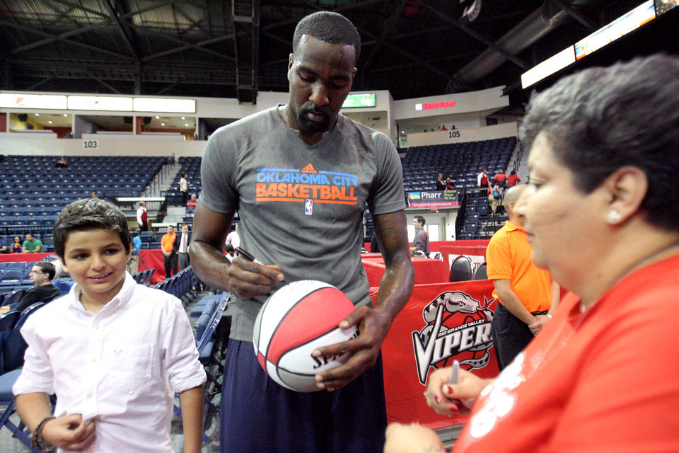 Oklahoma City Thunder\'s Serge Ibaka, center, of the Republic of Congo, autographs a basketball for fans before the start of their preseason NBA basketball game against the Houston Rockers, Wednesday, Oct. 10, 2012, in Hidalgo, Texas. (AP Photo/Delcia Lopez) ORG XMIT: TXDL101