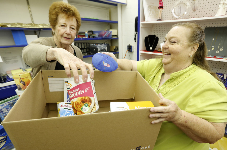Photo - Frances Marwil, left, manager of the Emanuel Synagogue gift shop, helps Sherri Jackson, a member of St. Benedict  Russian Orthodox Church, fill a box with food and other items related to the Jewish holiday of Passover.   PhotoS By Steve Gooch, The Oklahoman   Steve Gooch
