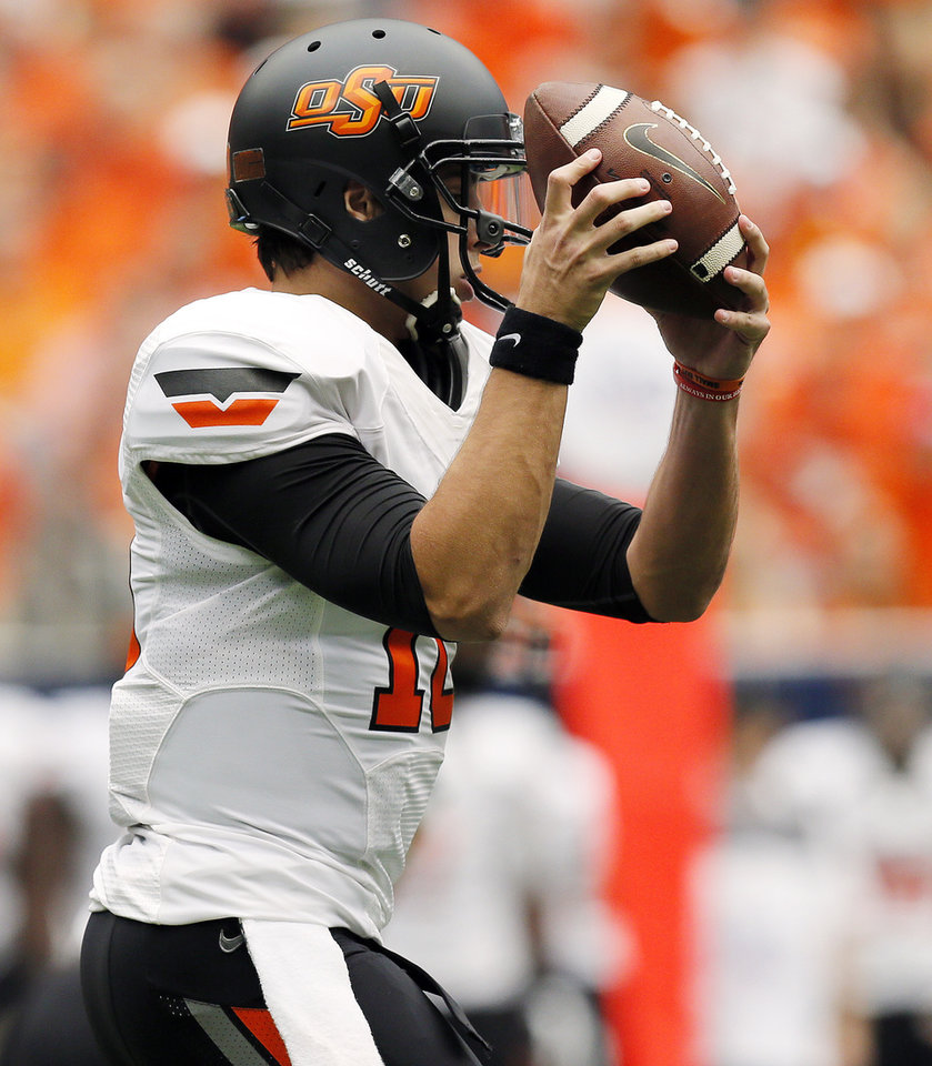 Oklahoma State quarterback Clint Chelf (10) takes a snap in the first quarter during the AdvoCare Texas Kickoff college football game between the Oklahoma State University Cowboys (OSU) and the Mississippi State University Bulldogs (MSU) at Reliant Stadium in Houston, Saturday, Aug. 31, 2013. Photo by Nate Billings, The Oklahoman