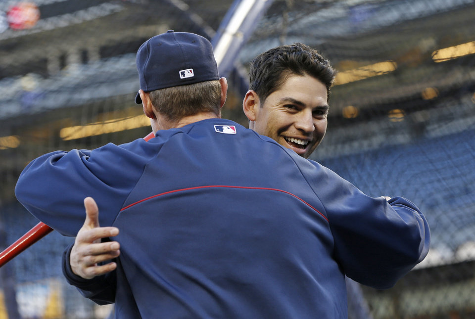 Photo - New York Yankees' Jacoby Ellsbury, right, embraces a Boston Red Sox coach before a baseball game at Yankee Stadium in New York, Thursday, April 10, 2014.  (AP Photo/Kathy Willens)