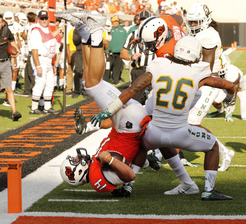 Photo - Oklahoma State's Taylor Cornelius (14) tries to leap into the end zone during the second half of a college football game between the Oklahoma State Cowboys (OSU) and the Southeastern Louisiana Lions at Boone Pickens Stadium in Stillwater, Okla., Saturday, Sept. 12, 2015. Photo by Steve Sisney, The Oklahoman