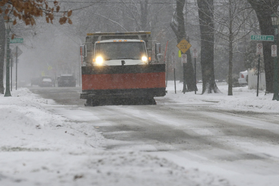 Photo - A snow plow drives down the street in Evanston, Ill., on Sunday, Dec. 22, 2013. Overnight snow carried over into Sunday morning, gradually tapering to flurries in the afternoon. The latest radar loops show the area of snow that brought up to 6 inches overnight to the I-39 corridor in north central Illinois and amounts ranging from a dusting to 3 inches to the north and northwest suburbs of Chicago is moving out of the area.  (AP Photo/Nam Y. Huh)