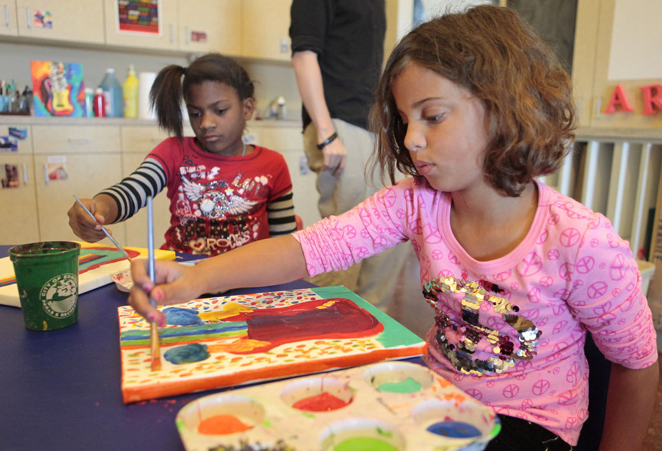 Far left: Angel Mosley, 9, and Jadyn Jefferson, 9, paint pictures of guitars.