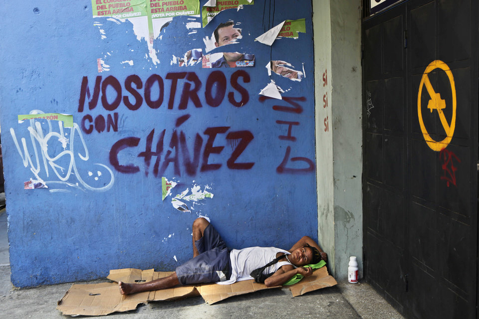 "Homeless Efrain Juanipas, 37, rests on a makeshift bed made from a a cardboard box next to graffiti that reads in English: ""We're with Chavez,"" in reference to Venezuela's President Hugo Chavez, in Caracas, Venezuela, Monday, Oct. 8, 2012. Chavez won re-election and a new endorsement of his socialist project Sunday, surviving his closest race yet after a bitter campaign against opposition candidate Henrique Capriles.(AP Photo/Rodrigo Abd)"
