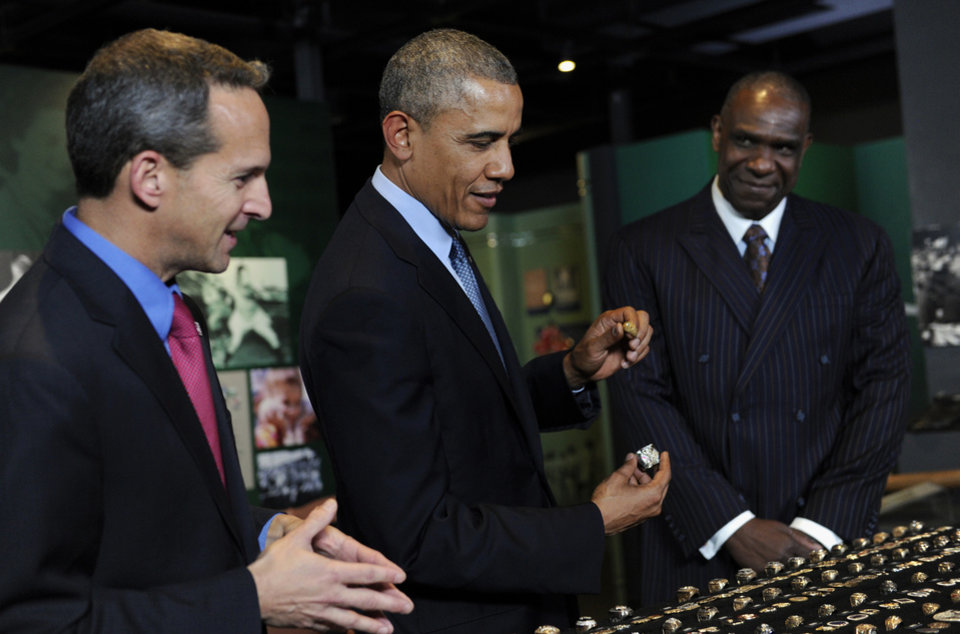Photo - President Barack Obama, accompanied by Baseball Hall of Fame President Jeff Idelson, left, and baseball hall of fame member Andre Dawson, looks over a collection of World Series rings during a tour the Baseball Hall of Fame in Cooperstown, N.Y., Thursday, May 22, 2014. President of the Hall of Fame, left, and Andre Dawson, inducted into the Hall of Fame in 2010. Obama visited the museum to highlight tourism and steps to help spur international visits to the 50 states. Obama said the overall U.S. economy and local businesses will benefit if it isn't a hassle for people from other countries to visit the U.S. and spend money at its hotels, restaurants, tourist destinations and other businesses. (AP Photo/Susan Walsh)