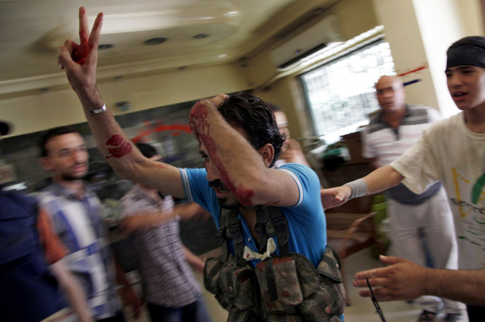 Photo -   An injured Syrian fighter flashes the victory sign as he arrives at a field hospital in Aleppo, Syria, Friday, Aug. 17, 2012. Rebel footholds in Aleppo have been the target of weeks of Syrian shelling and air attacks as part of wider offensives by President Bashar Assad's regime. Rebels have been driven from some areas, but the report of clashes near the airport suggests the battles could be shifting to new fronts. (AP Photo/ Khalil Hamra)
