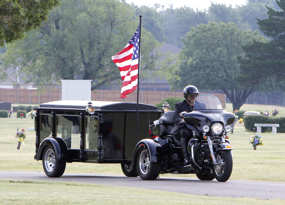 Photo - Brian Gray, who runs a motorcycle hearse business called Final Ride, rides his motorcycle at Chapel Hill Memorial Gardens Cemetery in Oklahoma City.  Photo By Paul Hellstern, The Oklahoman
