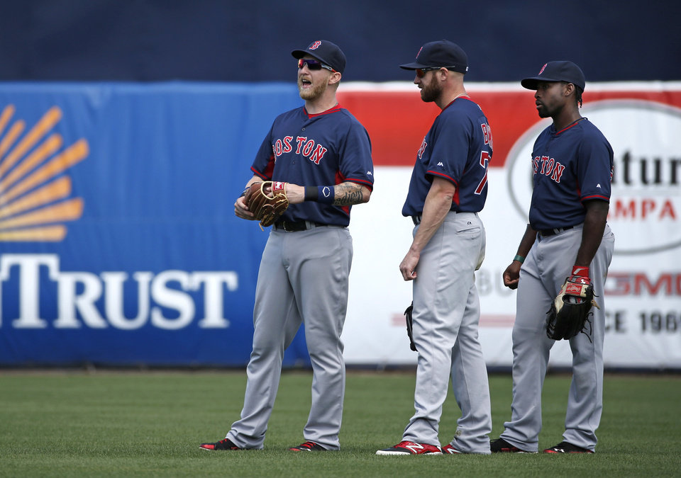 Photo - Boston Red Sox left fielder Mike Carp, left, calls to an umpire explaining that a swarm of bees have taken over left, field in the bottom of the third inning as Red Sox right fielder Corey Brown, center, and center fielder Jackie Bradley Jr. watch during a spring exhibition baseball game against the New York Yankees in Tampa, Fla., Tuesday, March 18, 2014.  The game was delayed seven minutes as groundskeepers eradicated the swarm with insecticide. (AP Photo/Kathy Willens)