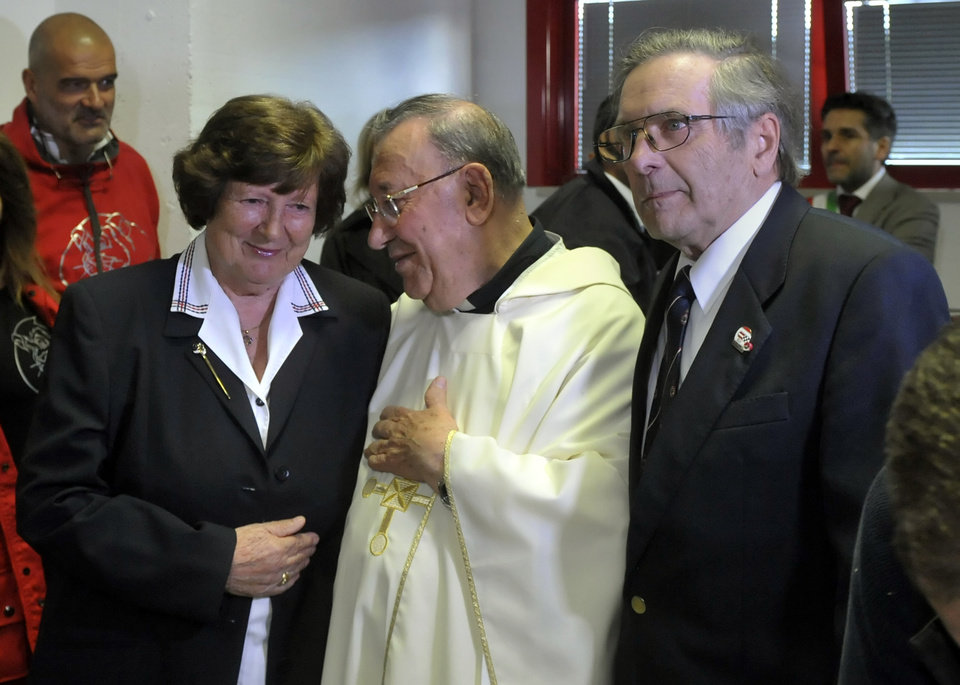 Photo - F1 drivers' chaplain Sergio Mantovani, center, stands in between Margit, left, and Rudolf Ratzenberger, parents of former Formula one driver Roland Ratzenberger, in Imola, Italy, Wednesday, April 30, 2014. Fans and family members are gathering this week to pay their respects to former Formula One drivers Ayrton Senna and Roland Ratzenberger on the 20th anniversary of their deaths. F1 drivers' chaplain Sergio Mantovani celebrated a memorial mass Wednesday in a packed room beside pit lane at the Enzo and Dino Ferrari track that once hosted the San Marino Grand Prix. (AP Photo/Marco Vasini)