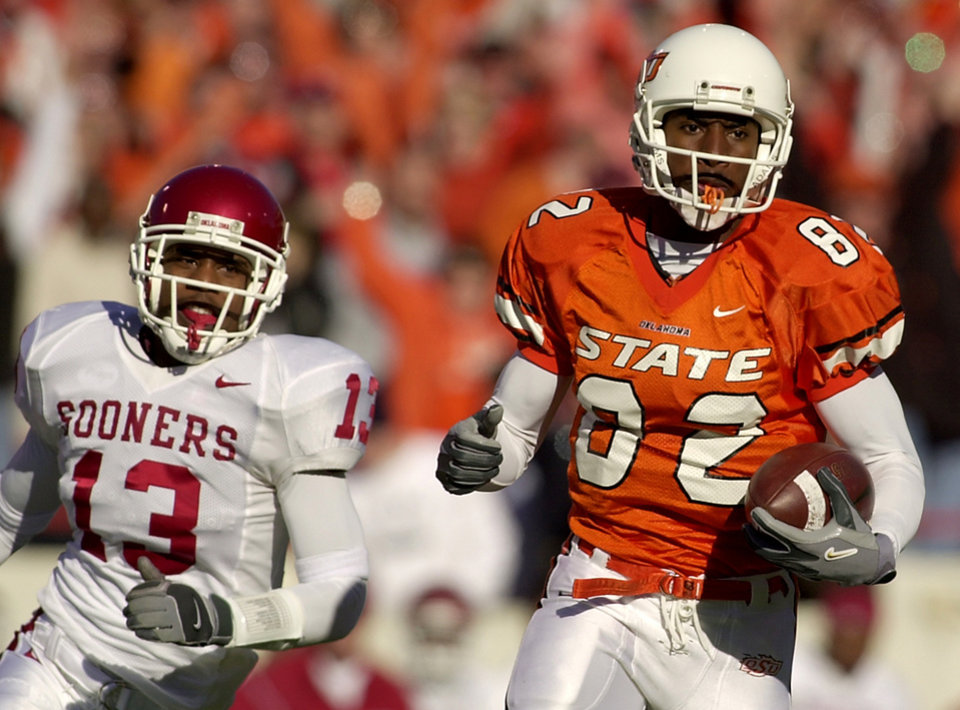 OSU wide receiver Rashaun Woods runs after a catch for a touchdown as OU's Eric Bassey pursues during the Oklahoma State vs. Oklahoma Bedlam college football at OSU's Lewis Field in Stillwater, Okla., Saturday, November 30, 2002. Staff photo by Nate Billings.