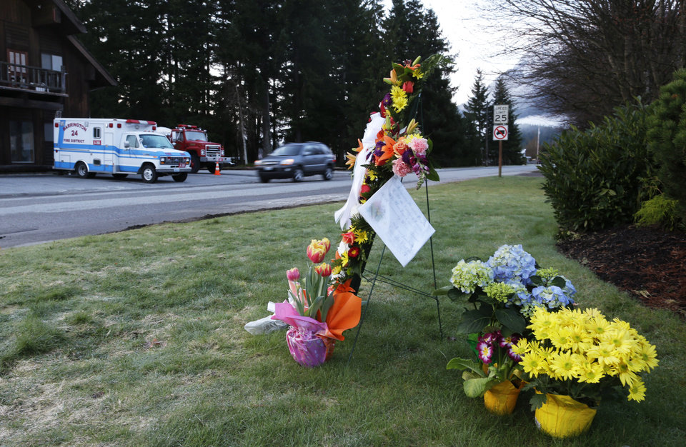 Photo - A car passes a small flower memorial, Monday, March 31, 2014, at the fire station in Darrington, Wash., at the beginning of another week of searching for victims of the massive mudslide that hit the nearby community of Oso,Wash.  Crews have cleared a path through the muck and devastation wrought by Washington's deadly mudslide, making the painstaking search for victims easier. The makeshift road completed over the weekend links one side of the 300-acre debris field to the other. (AP Photo/Ted S. Warren)