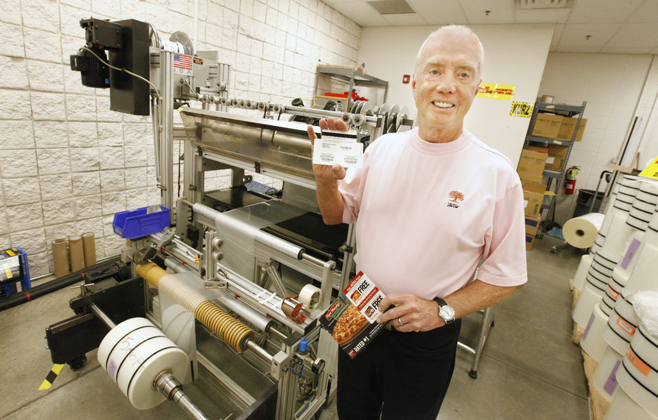 Photo - Ron Goade, founder of SSI Technologies, is seen with the magnetic tape machine at his business in Edmond. Photo by Paul B. Southerland, The Oklahoman  PAUL B. SOUTHERLAND