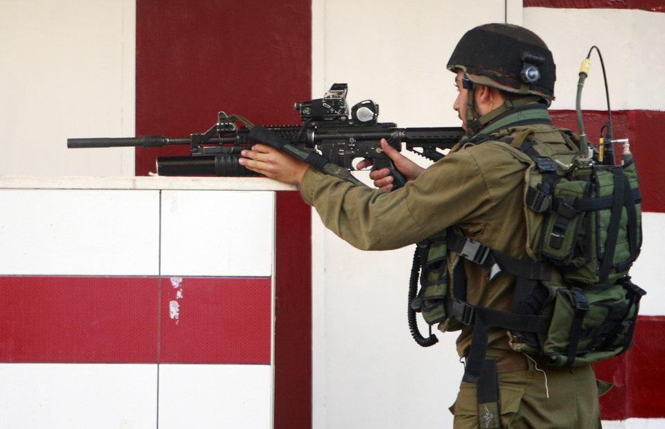 Photo - An Israeli army soldier aims his weapon during clashes with Palestinians in the early morning in the West Bank city of Jenin, Wednesday, July 2, 2014. Tensions have mounted between Israel and the Palestinians after the bodies of three Israeli teens were found in the West Bank more than two weeks after they went missing. (AP Photo/Mohammed Ballas)