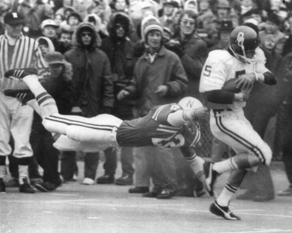 Photo - OU COLLEGE FOOTBALL: 11/24/74. OU's Steve Davis eludes a diving Nebraska defender. Staff photo by J. Pat Carter.