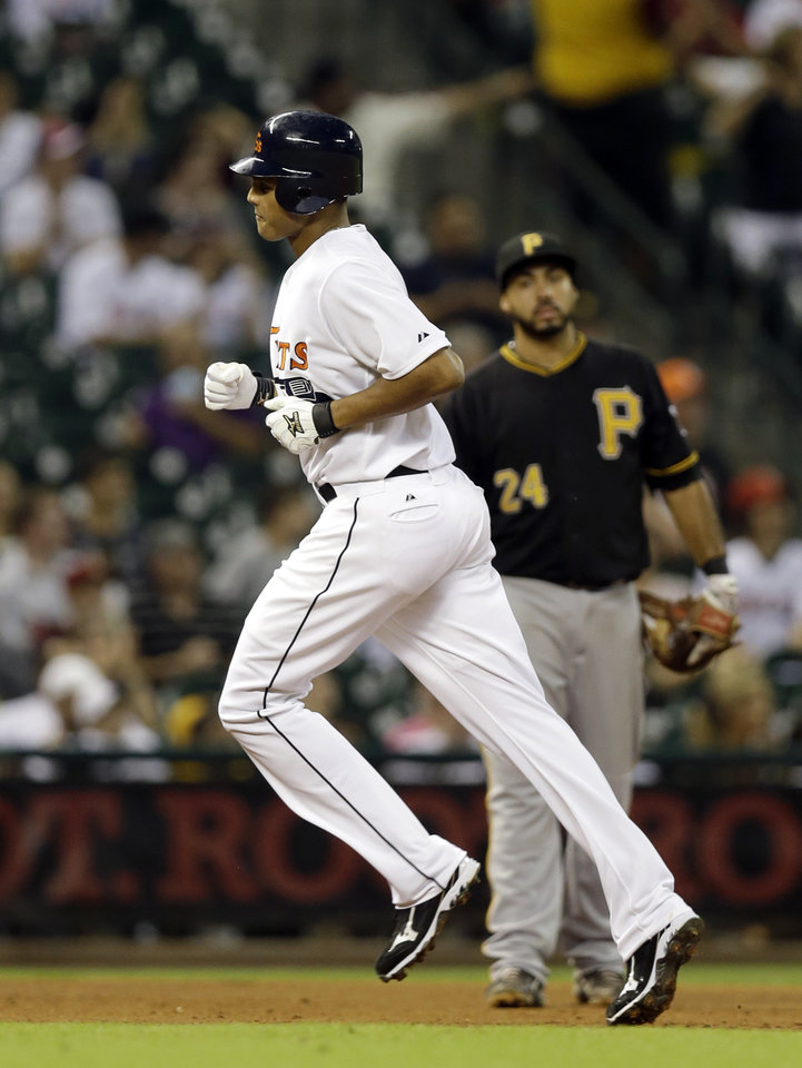 Photo -   Houston Astros' Justin Maxwell, left, runs past Pittsburgh Pirates third baseman Pedro Alvarez (24) after hitting a home run during the sixth inning of a baseball game on Friday, Sept. 21, 2012, in Houston. (AP Photo/David J. Phillip)