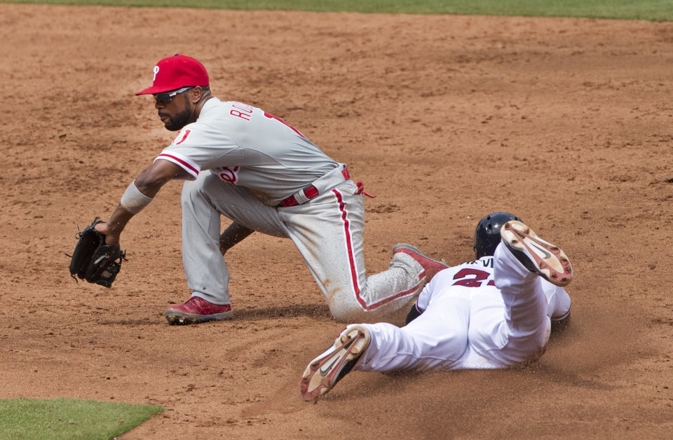 Photo - Atlanta Braves right fielder Jason Heyward (22) steals second base as Philadelphia Phillies shortstop Jimmy Rollins (11) handles the throw in the third inning of a baseball game Monday, Sept. 1, 2014, in Atlanta. (AP Photo/John Bazemore)