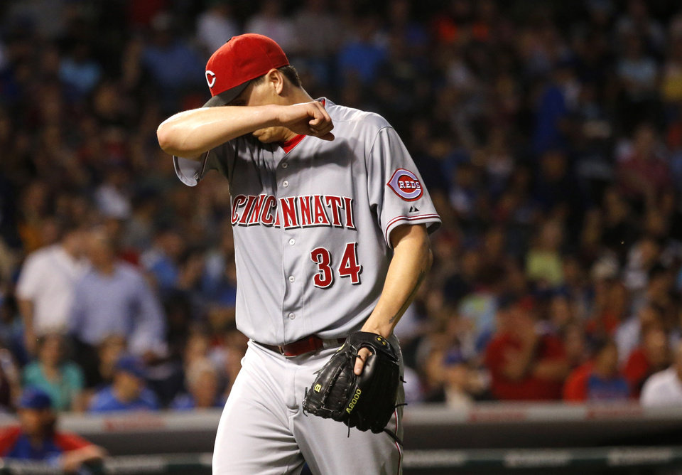 Photo - Cincinnati Reds starting pitcher Homer Bailey wipes the sweat from his face as he heads to the dugout after the third inning of a baseball game against the Chicago Cubs on Tuesday, June 24, 2014, in Chicago. (AP Photo/Charles Rex Arbogast)