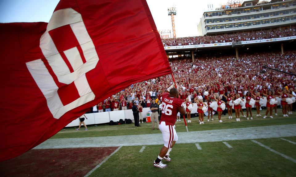 Photo - Oklahoma's Adrian Taylor carries the OU flag around the Cotton Bowl after the Sooners' 28-20 win over Texas in the Red River Rivalry college football game between the University of Oklahoma Sooners (OU) and the University of Texas Longhorns (UT) at the Cotton Bowl on Saturday, Oct. 2, 2010, in Dallas, Texas.   Photo by Chris Landsberger, The Oklahoman