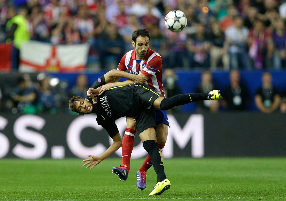 Photo - Barcelona's Neymar, left, fights for the ball with Atletico's Juanfran during the Champions League quarterfinal second leg soccer match between Atletico Madrid and FC Barcelona in the Vicente Calderon stadium in Madrid, Spain, Wednesday, April 9, 2014. (AP Photo/Paul White)