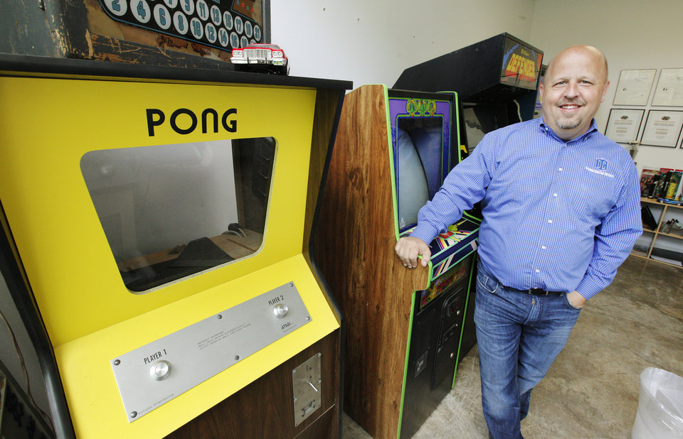 Photo - Above:  Associate professor Jeff Price, director of gaming and animation, stands with with early model video games — including the first PONG from the 1970s — in his office at Oklahoma Christian University in Oklahoma City.  PAUL B. SOUTHERLAND