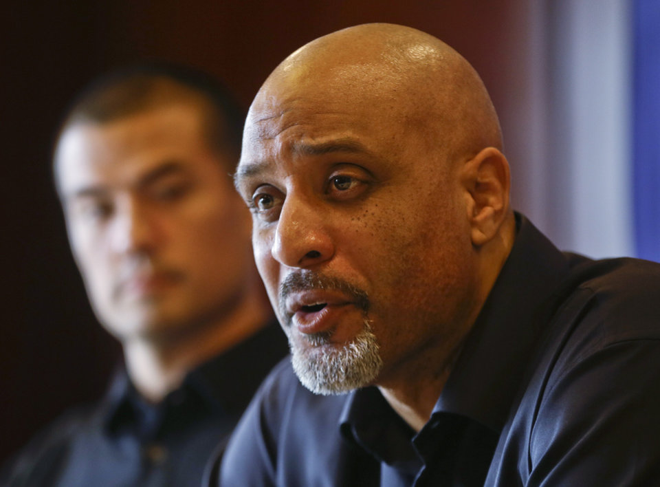 Photo - FILE - In this Dec. 3, 2013, file photo, Tony Clark, executive director of the Major League Baseball Players Association, answers questions during a news conference in San Diego. At rear is executive board member Jeremy Guthrie. People familiar with the negotiations tell The Associated Press that baseball players and management hope to reach a new drug agreement this week that would increase initial penalties for muscle-building steroids and decrease suspensions for some positive tests caused by unintentional use.  (AP Photo/Lenny Ignelzi, File)