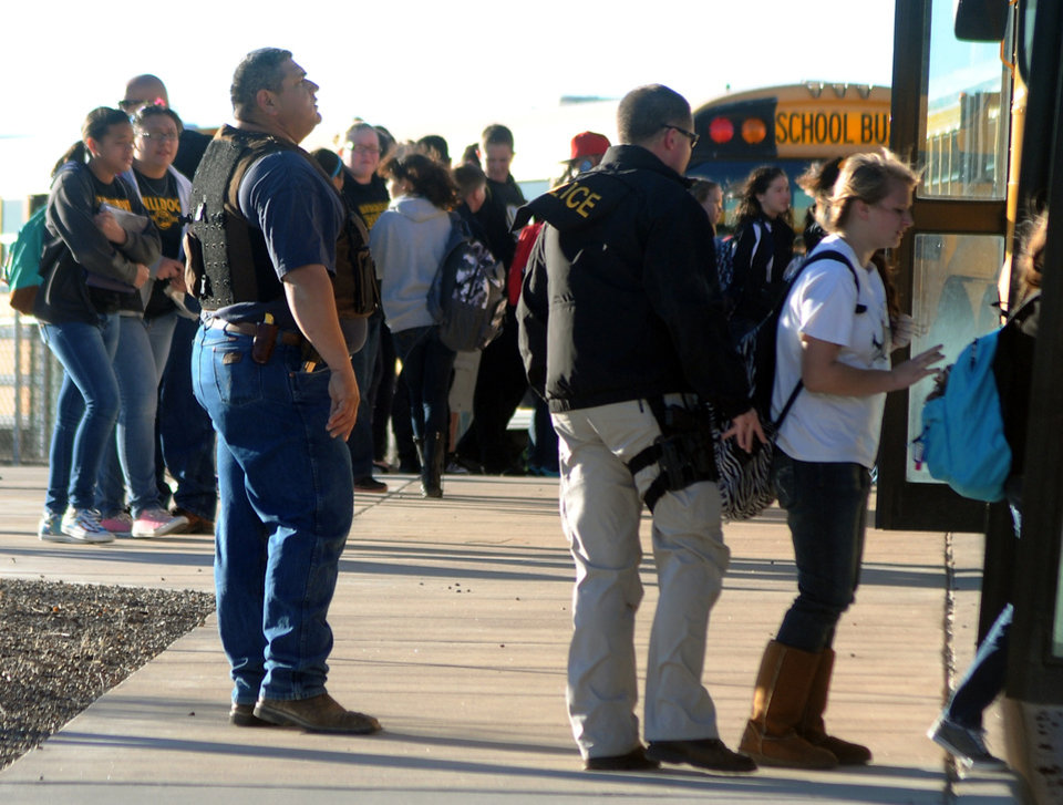 Photo - Authorities stand guard as students are escorted from Berrendo Middle School after a shooting, Tuesday, Jan. 14, 2014, in Roswell, N.M. A shooter opened fire at the middle school, injuring at least two students before being taken into custody. Roswell police said the school was placed on lockdown. (AP Photo/Roswell Daily Record, Mark Wilson)