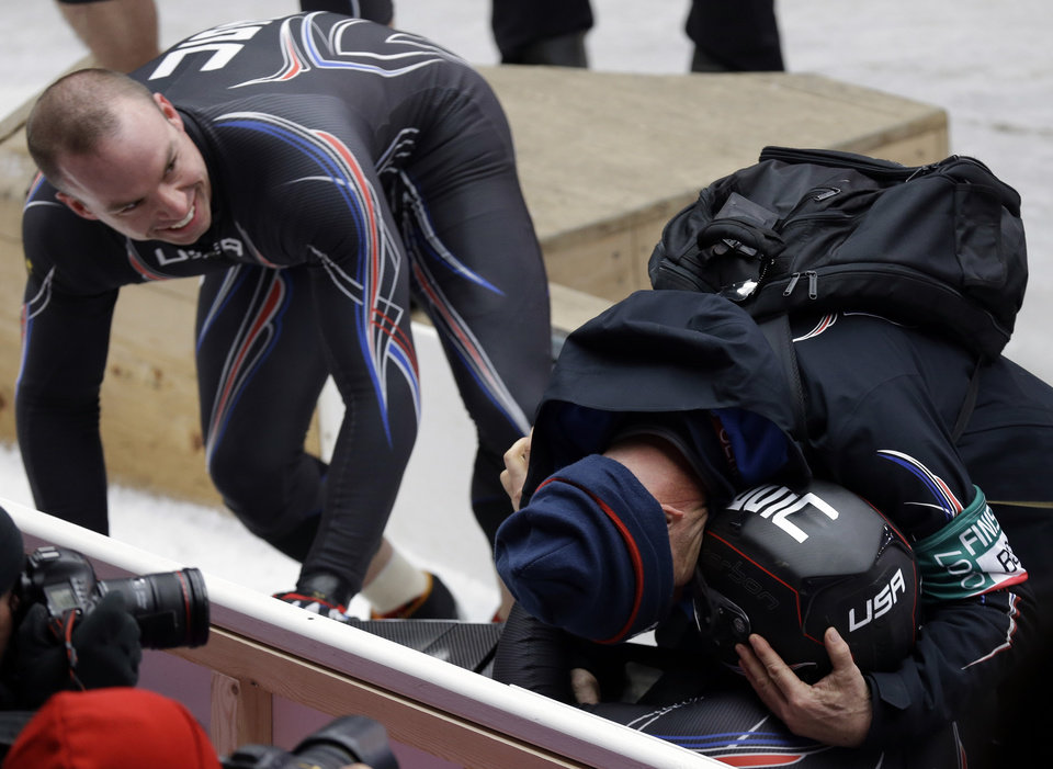 Photo - The team from the United States USA-1, pilot Steven Holcomb gets hugged by teammates after his bronze medal finish during the men's two-man bobsled competition at the 2014 Winter Olympics, Monday, Feb. 17, 2014, in Krasnaya Polyana, Russia. (AP Photo/Natacha Pisarenko)