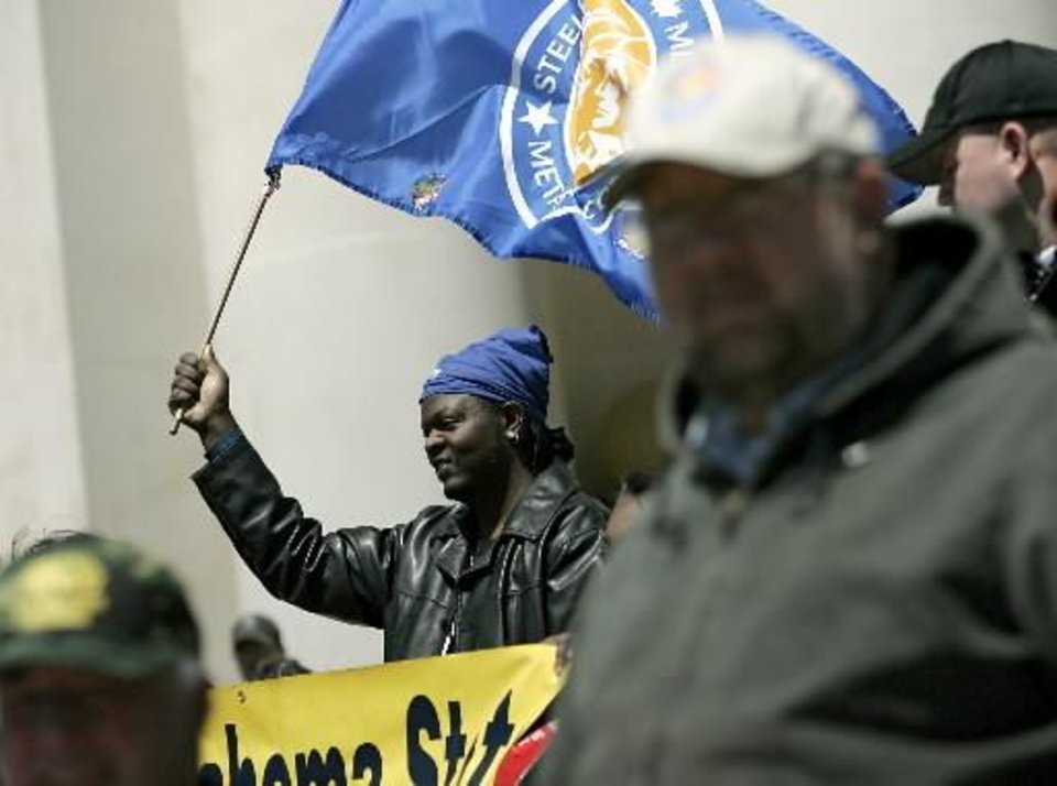 David Sawyer, a Steelworker with Local 4430 in Tulsa, holds a flag as during a rally outside the Oklahoma State Capitol in Oklahoma City today. Photo by John Clanton